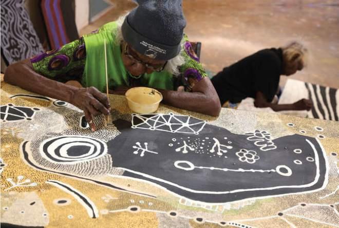 Martha MacDonald Napaltjarri (in foreground) and Mona Nangala painting at Papunya Tjupi art centre, Papunya, 2015. Photo: Helen Puckey